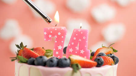 Birthday cake number 74, pink candle on beautiful cake with berries and lighter with fire against background of white clouds and pink sky. Close-up