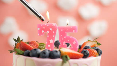 Birthday cake number 75, pink candle on beautiful cake with berries and lighter with fire against background of white clouds and pink sky. Close-up