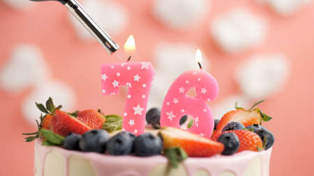 Birthday cake number 76, pink candle on beautiful cake with berries and lighter with fire against background of white clouds and pink sky. Close-up Imagens