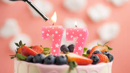 Birthday cake number 77, pink candle on beautiful cake with berries and lighter with fire against background of white clouds and pink sky. Close-up