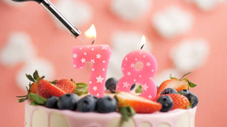 Birthday cake number 78, pink candle on beautiful cake with berries and lighter with fire against background of white clouds and pink sky. Close-up