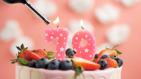 Birthday cake number 79, pink candle on beautiful cake with berries and lighter with fire against background of white clouds and pink sky. Close-up Imagens