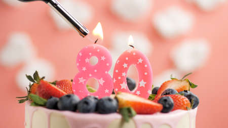 Birthday cake number 80, pink candle on beautiful cake with berries and lighter with fire against background of white clouds and pink sky. Close-up Imagens