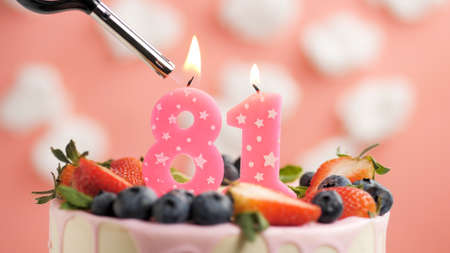 Birthday cake number 81, pink candle on beautiful cake with berries and lighter with fire against background of white clouds and pink sky. Close-up