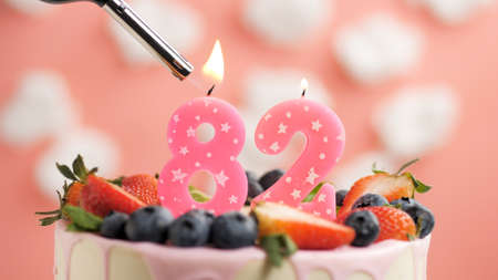 Birthday cake number 82, pink candle on beautiful cake with berries and lighter with fire against background of white clouds and pink sky. Close-up Imagens