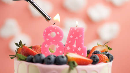 Birthday cake number 84, pink candle on beautiful cake with berries and lighter with fire against background of white clouds and pink sky. Close-up