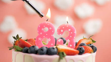 Birthday cake number 83, pink candle on beautiful cake with berries and lighter with fire against background of white clouds and pink sky. Close-up