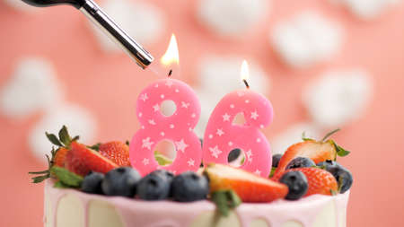 Birthday cake number 86, pink candle on beautiful cake with berries and lighter with fire against background of white clouds and pink sky. Close-up Imagens