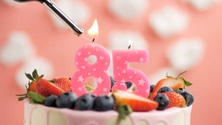 Birthday cake number 85, pink candle on beautiful cake with berries and lighter with fire against background of white clouds and pink sky. Close-up Imagens