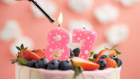 Birthday cake number 87, pink candle on beautiful cake with berries and lighter with fire against background of white clouds and pink sky. Close-up