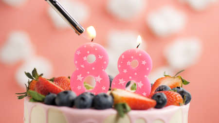 Birthday cake number 88, pink candle on beautiful cake with berries and lighter with fire against background of white clouds and pink sky. Close-up