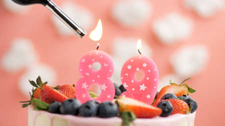 Birthday cake number 89, pink candle on beautiful cake with berries and lighter with fire against background of white clouds and pink sky. Close-up Imagens