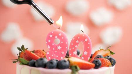 Birthday cake number 90, pink candle on beautiful cake with berries and lighter with fire against background of white clouds and pink sky. Close-up
