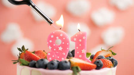 Birthday cake number 91, pink candle on beautiful cake with berries and lighter with fire against background of white clouds and pink sky. Close-up