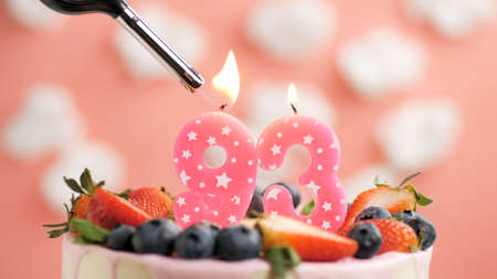 Birthday cake number 93, pink candle on beautiful cake with berries and lighter with fire against background of white clouds and pink sky. Close-up