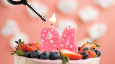 Birthday cake number 94, pink candle on beautiful cake with berries and lighter with fire against background of white clouds and pink sky. Close-up