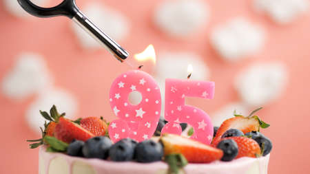 Birthday cake number 95, pink candle on beautiful cake with berries and lighter with fire against background of white clouds and pink sky. Close-up