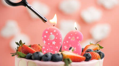 Birthday cake number 96, pink candle on beautiful cake with berries and lighter with fire against background of white clouds and pink sky. Close-up