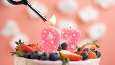 Birthday cake number 97, pink candle on beautiful cake with berries and lighter with fire against background of white clouds and pink sky. Close-up Imagens