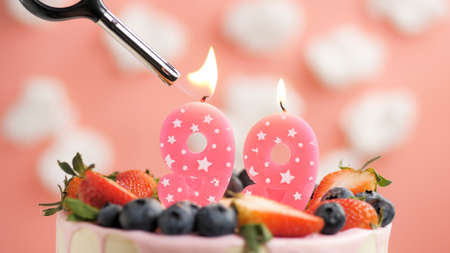 Birthday cake number 99, pink candle on beautiful cake with berries and lighter with fire against background of white clouds and pink sky. Close-up
