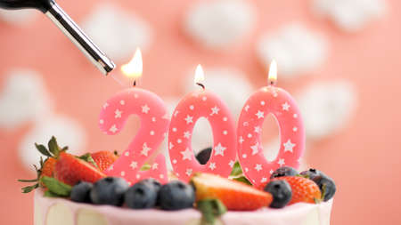 Birthday cake number 200, pink candle on beautiful cake with berries and lighter with fire against background of white clouds and pink sky. Close-up Imagens