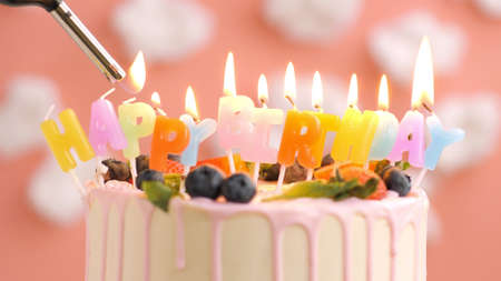Birthday cake with candle title Happy Birthday on beautiful cake with berries and lighter with fire against background of white clouds and pink sky. Close-up