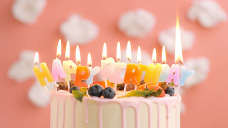 Birthday cake with candle title Happy Birthday on beautiful cake with berries background of white clouds and pink sky. Close-up Imagens