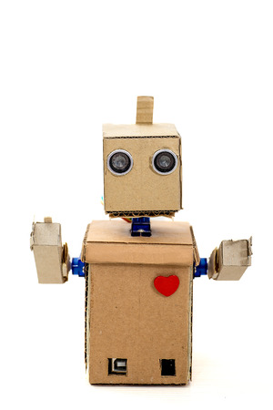 cardboard robot with a red heart is on the white background