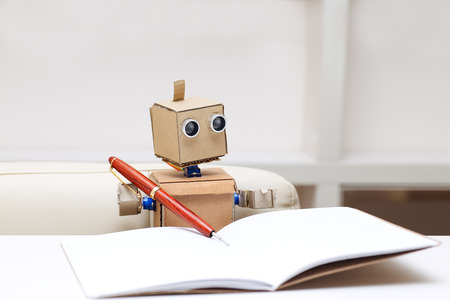 Robot writes sitting at table in writing