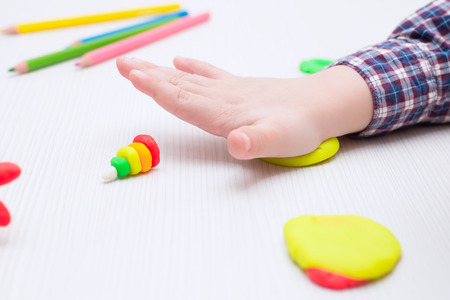 child busy playing with plasticine