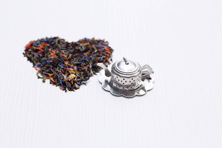 metal teapot and shape of the heart of the tea leaves