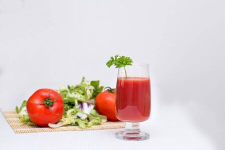 tomato juice: tomato juice in a glass with tomatoes and greens
