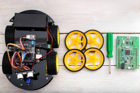 robotics parts. four-wheel drive, otvertkzelenogo tsveat, printed circuit board lying on a wooden table