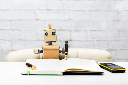Robot sits at the table and writes a pen in his notebook 스톡 콘텐츠