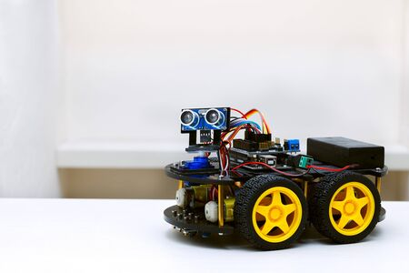 Robot with four wheels stands on a white table