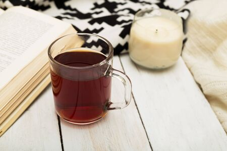 A cup of warm tea, a warm blanket, a candle and a book on a wooden background Stock Photo