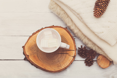 Cup with hot chocolate and marshmallows, a row of cones and a stack of knitted things on a white wooden background Stock Photo