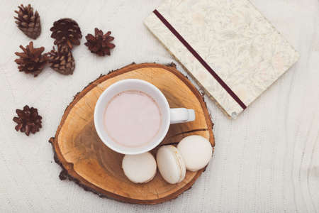 hygge. A cup of cocoa stands on a wooden tray, beside lie cones