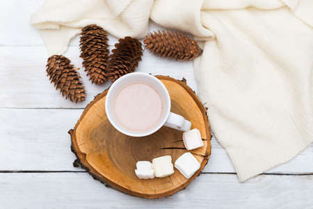 Cup with hot chocolate and marshmallows, a row of cones and a knitted blanket on a white wooden background
