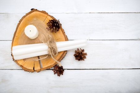 hygge. Cones and candles lie on a wooden stand on a white wooden background.