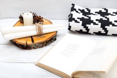 Hygge. Cozy rest with a book, candles and a blanket Stock Photo