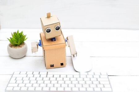 robot - office worker and his workplace with a keyboard and mouse Banco de Imagens