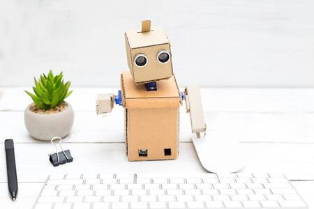 The robot works behind the computer on the keyboard Stock Photo