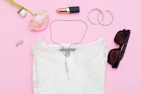 Womens accessories and jewelry on a pink background. Flat lay Stock Photo