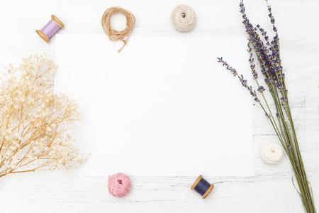 Witte lege kaart met bloemen en lint op houten achtergrond. Productmodel