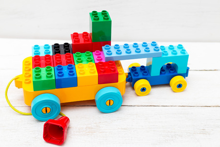 A toy car of cubes of lego on a wooden background. Educational toys Zdjęcie Seryjne