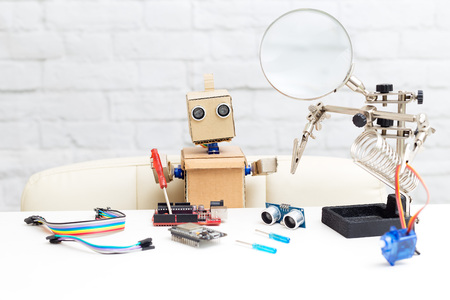 The robot with hands sits at the table and near the working tools. Artificial Intelligence Stock Photo