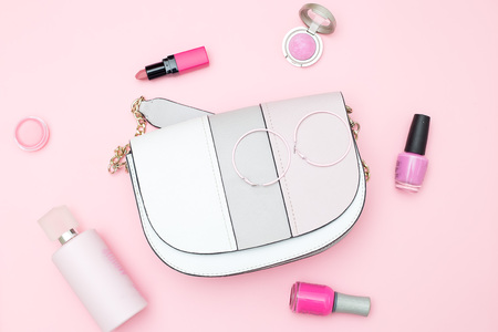 Handbag and beauty on a pink background. Flat lay