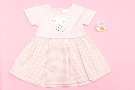 Baby pink dress for a girl on a pink background. Flat lay Stock Photo