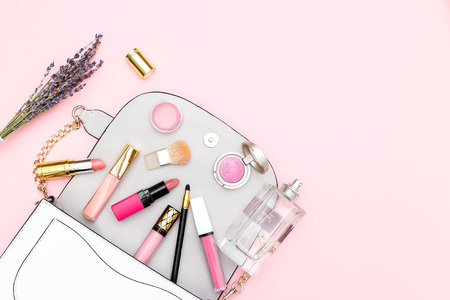 Feminine handbag and cosmetics set on a pink background. Copy space